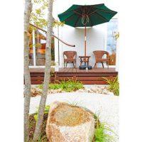 グリーンの傘がお洒落なテラスのある庭